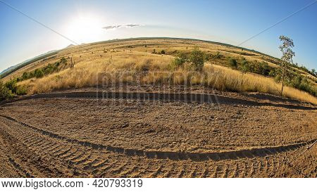 Late Evening Light On The Curved Country Horizon With Dirt Road Frontage, Photographed With A Fishey