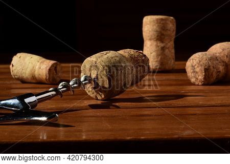 Close Up Of A Classic Corkscrew With A Wine Cork At The Tip Is On A Wooden Brown Table Surface. Some