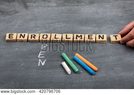 Open Enrollment Concept. Letters Of The Alphabet And Colored Pieces Of Chalk On A Black Chalkboard