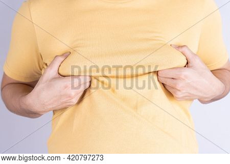 Fat Man Holding Excessive Fat Boobs Isolated Grey Background.
