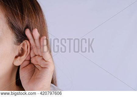 Woman Hearing Loss Or Hard Of Hearing And Cupping Her Hand Behind Her Ear Isolate Grey Background, D