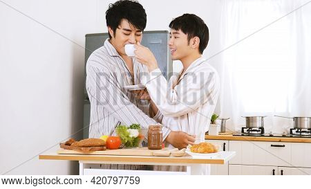 Gay Couple Homosexual Cookking Together In The Kitchen Make A Breakfast Relation Fall In Love. Lgbtq