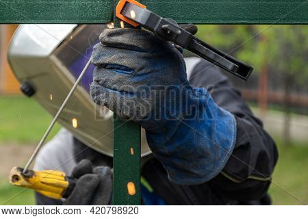 A Young  Man Welder In  Uniform, Welding Mask And Welders Leathers, Weld  Metal  With A Arc Welding
