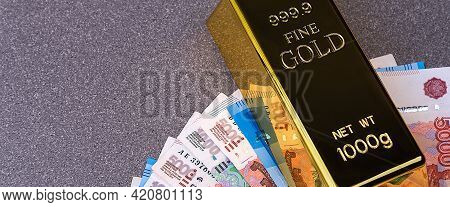 Gold Bullion Ingot And Russian Ruble Banknotes. The Banknotes Are Spread Out In A Fan And Pinned Dow