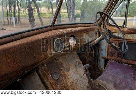 Interior Showing Dashboard, Steering Wheel And Seat Of Rusted Truck Wreck