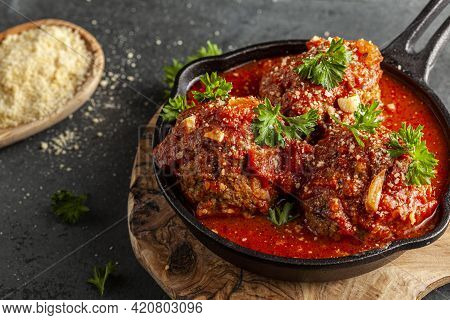 Close Up View Of Three Traditional Large Italian Meatballs In Sizzling Tomato Sauce In Cast Iron Pan