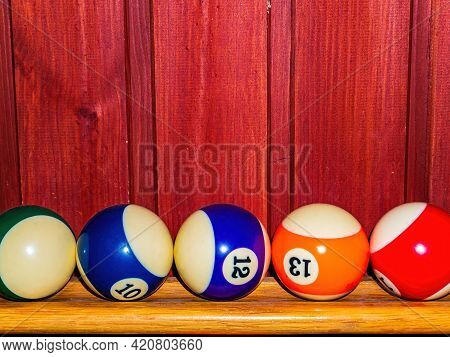 Colored Billiard Balls On A Wooden Shelf.