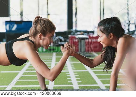 Two Young Friends Give Five Between Sport Training And Yoga In Fitness Gym Together. Asian Couple Of