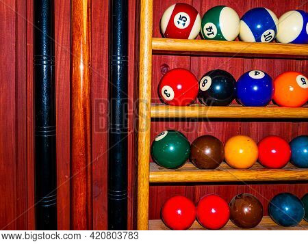 Colored Billiard Balls And A Cue On A Wooden Shelf. Billiard Ball. Wooden Shelf. Numbered Balls. Gam