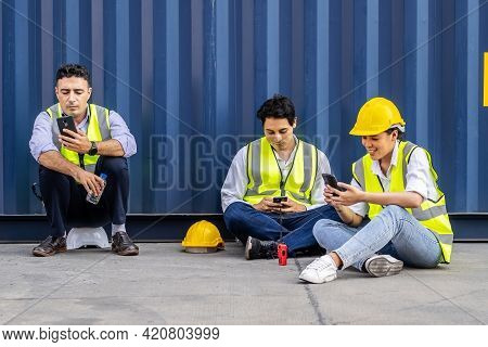 Group Of Workers Playing, Online Chatting Or Browsing On Mobile Phone While Taking A Break At Constr