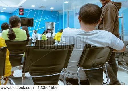 Back View Of Male Customers Sitting And Wait In Queues To Financial Transactions With The Bank Staff