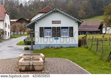 Swiss Alps village in Canton Jura with characteristic houses on a cloudy day. Nature, nobody inside