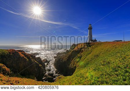 Artistic Sun Flare And Waves Crashing On The Shore By Pigeon Point Lighthouse On Northern California