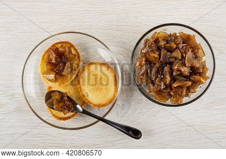 Few Small Pancakes With Jam, Teaspoon In Transparent Saucer, Bowl Of Apple Jam With Cinnamon On Wood