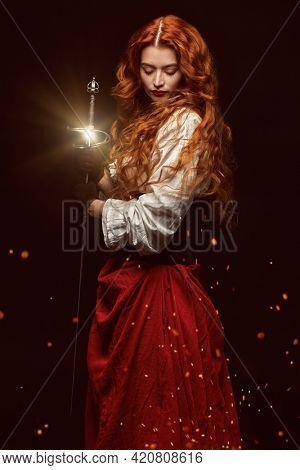 Beautiful courageous woman with long foxy hair posing with a battle epee (rapier) on a black background with fire sparks. Historical reconstruction of the 16-17th centuries.