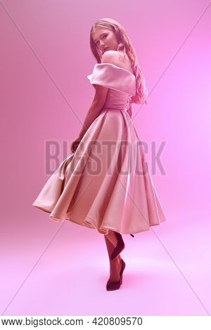 Evening fashion. A beautiful girl in an elegant evening dress poses at the studio in gentle pink light.