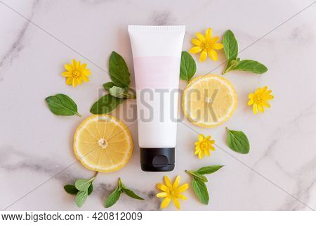 Natural Vitamin C Skincare Product With Fresh Juicy Lemon Fruit Slices On Marble Background. Moistur