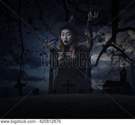 Mystery Halloween Witch Standing Over Grass, Dead Tree, Cross, Birds With Church Over Spooky Cloudy