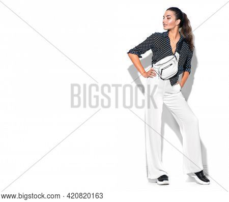 Beauty model girl posing in trendy fashionable spring clothes, wear, apparel.  Beautiful young brunette woman in trendy outfit, fashion accessories. Isolated on white background. Urban street style.