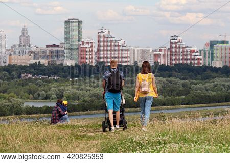 Couple With Baby Pram Walking On Top Of A Hill On Background Of Summer City And Buildings Under Cons