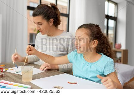 family, motherhood and leisure concept - happy smiling mother spending time with her little daughter drawing or painting wooden chipboard items with colors at home
