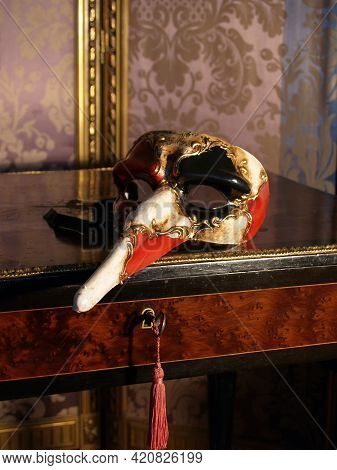 Traditional Venetian Carnival Mask Seen From The Side On A Vintage Table - Old Fashioned Screen With
