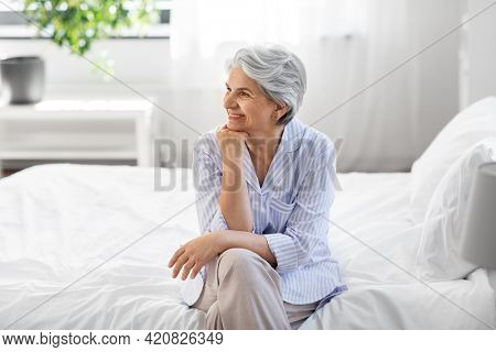 old age and people concept - happy smiling senior woman in pajamas sitting on bed at home bedroom