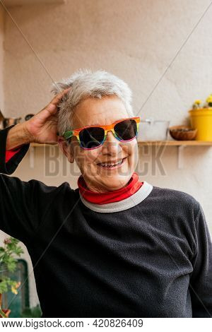 Vertical Portrait Of Older Lesbian Woman With Short Gray Hair Wearing Rainbow Pride Flag Sunglasses
