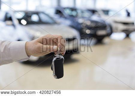 Salesman Holding Keys To A New Car. Car Auto Dealership. Modern And Prestigious Vehicles.
