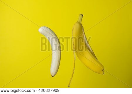 Banana On A Yellow Background. Bright Fruit. Peeled Banana Next To The Peel On A Colored Background