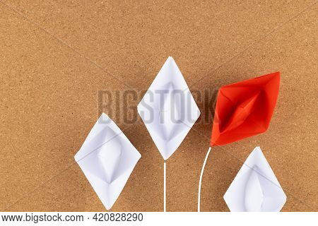 A Group Of White Paper Ship Pointing In One Direction And One Red Paper Ship. Business Behind An Inn