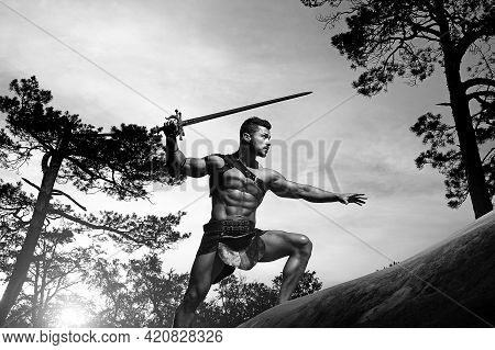 Power In Every Move. Low Angle Monochrome Shot Of A Stunning Masculine Young Warrior With A Muscular
