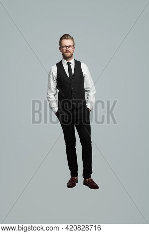 Self Assured Male Entrepreneur In Classy Outfit Standing With Hands In Pockets On Gray Background In