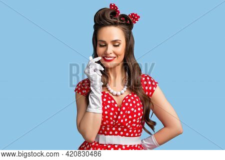 Sensual Young Pinup Woman In Retro Red Polka Dot Dress Touching Her Face And Smiling Mysteriously On