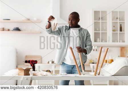 Puzzled African American Man Holding Package With Details, Assembling Chair With Instructions In Kit