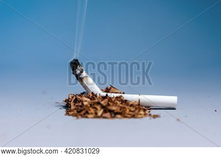 World Tobacco Control Day. A Broken, Smoking Cigarette Lies In A Pile Of Tobacco On A Blue Backgroun