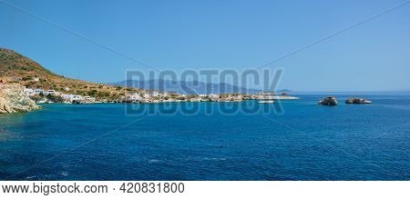 Panorama of Greek fishing village with traditional whitewashed white houses on Milos island view from Aegean sea in Greece