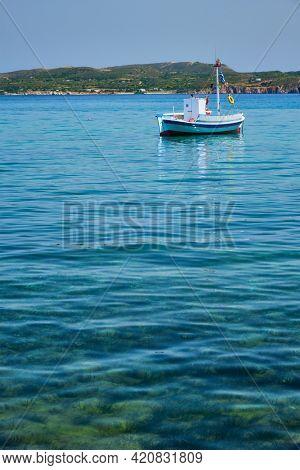 Greek fishing boat moored in blue waters of Aegean sea in harbor of near Milos island, Greece