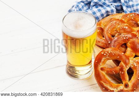 Lager beer mug and fresh baked homemade pretzel with sea salt. Classic beer snack. With copy space