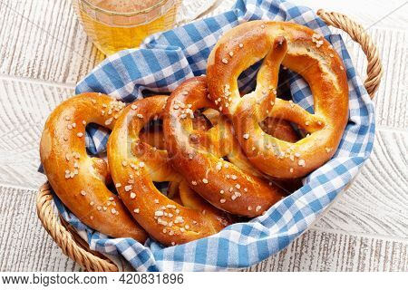Lager beer mug and fresh baked homemade pretzel with sea salt on wooden table. Classic beer snack