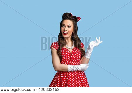 Seductive Young Woman In Pinup Retro Style Outfit Looking Aside And Smiling On Blue Studio Backgroun