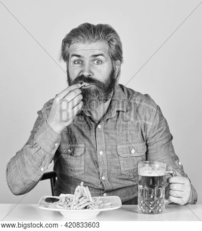 Lazy Man Enjoying Fresh Beer And Junk Food. Man With Fast Food. Beer And French Fries In Restaurant.