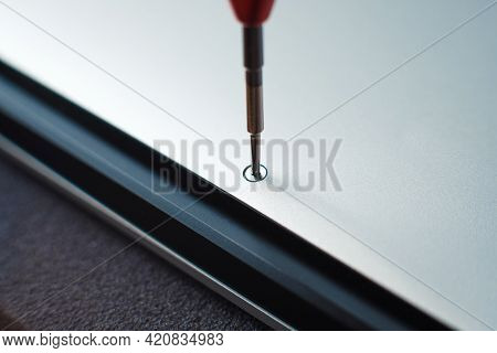 Close Up - Master Unscrewing Small Screw With Screwdriver Tool, Disassembling And Repairing Of Broke