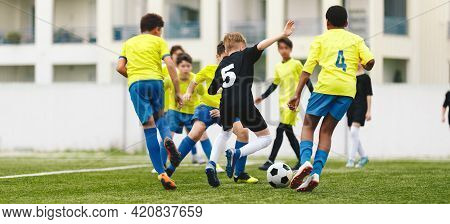 Multiracial Group Of Soccer Kids Playing Tournament Game. Happy Children Kicking Football Ball On Gr