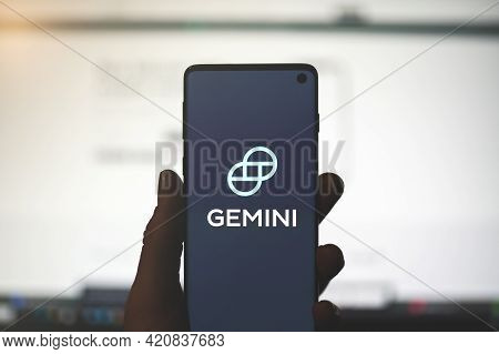 Swansea, Uk - May 2, 2021: Man Holding A Smartphone With Gemini App Logo With Blurred Website Backgr