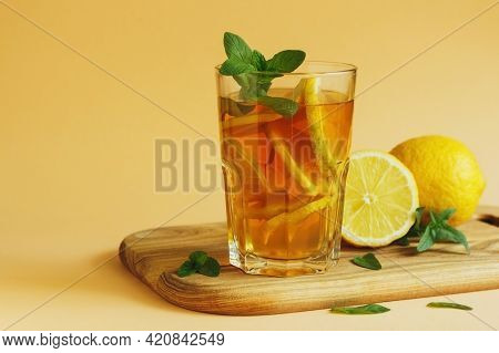 Fresh And Cold Ice Tea With Lemon And Mint On Yellow Background