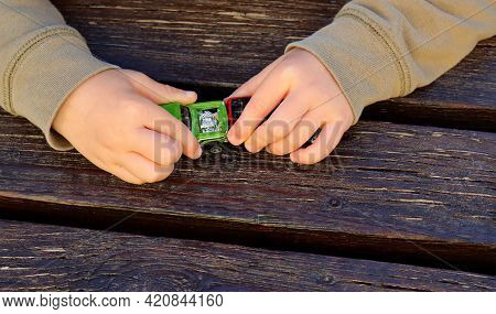 Children's Hands With Toy Cars On A Wooden Background. A Child Plays With A Children's Model Car.