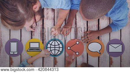 Composition of digital online icons over male teacher and school children drawing in background. global networks and digital interface concept digitally generated image.