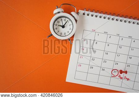 Top View Of White Analog Clock, Red Pushpin, Red Circle And Pay Day Text Marked The Last Day Of Mont