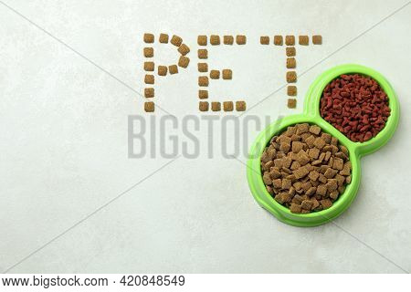 Word Pet Made Of Feed And Bowls Of Feed On White Textured Background